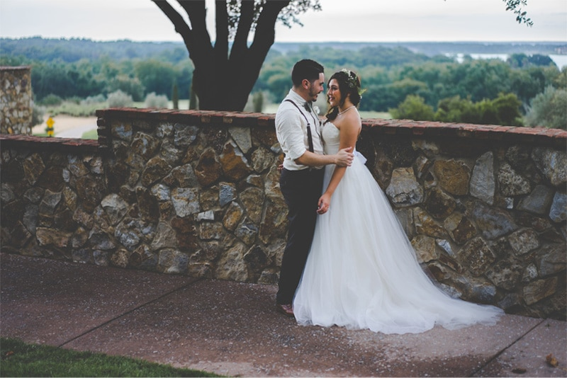 bride and groom in front of rock wall for portraits after their wedding ceremony