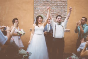 groom with arms in the air after being pronounced husband and wife
