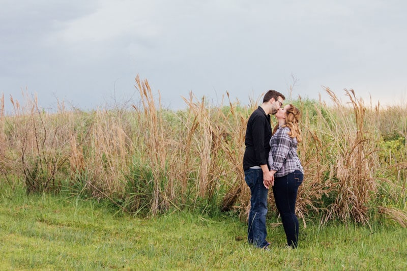 couple kissing next to marshy lakefront