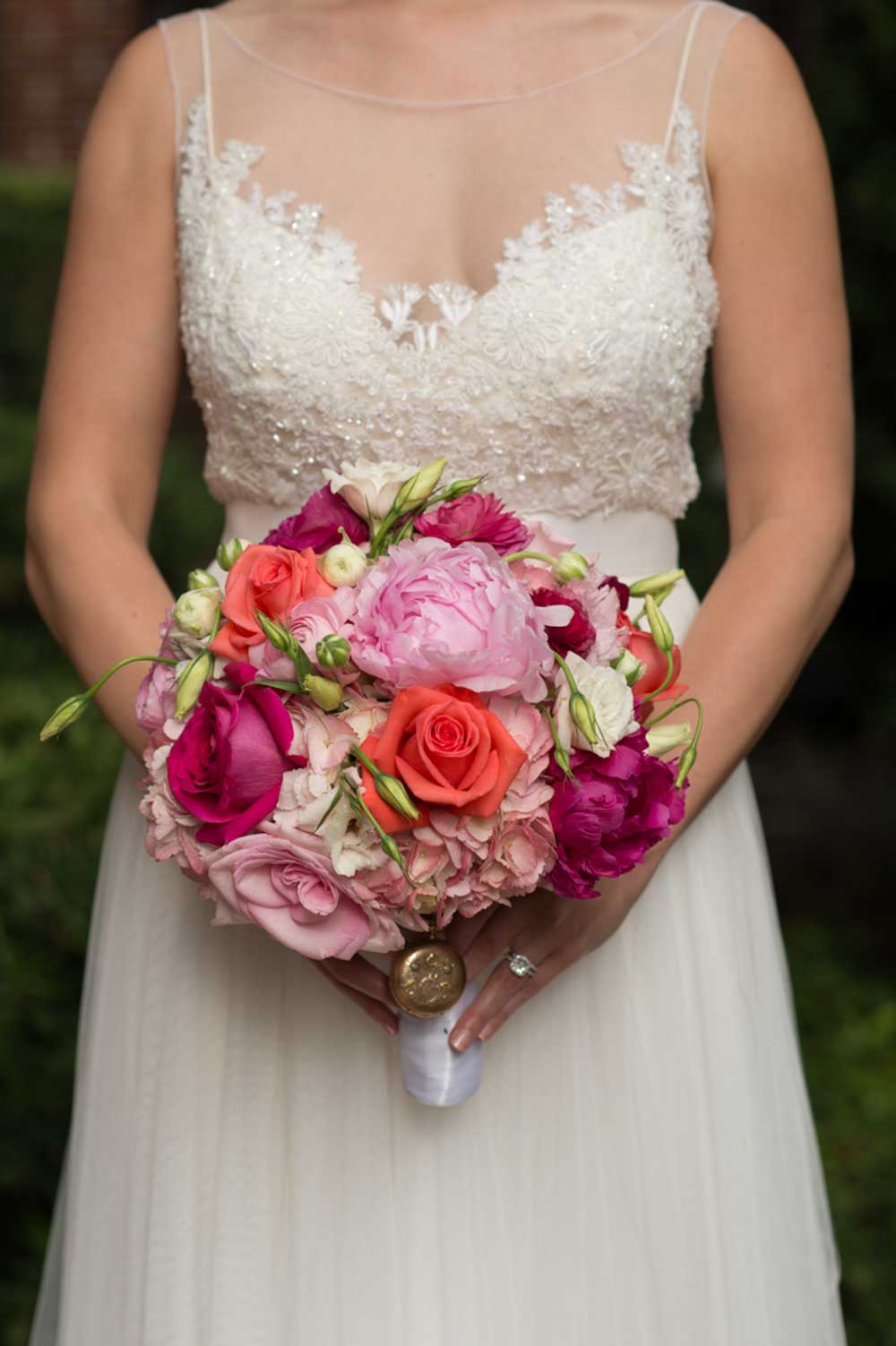 bride holding vibrant fuchsia, orange and pink bridal bouquet