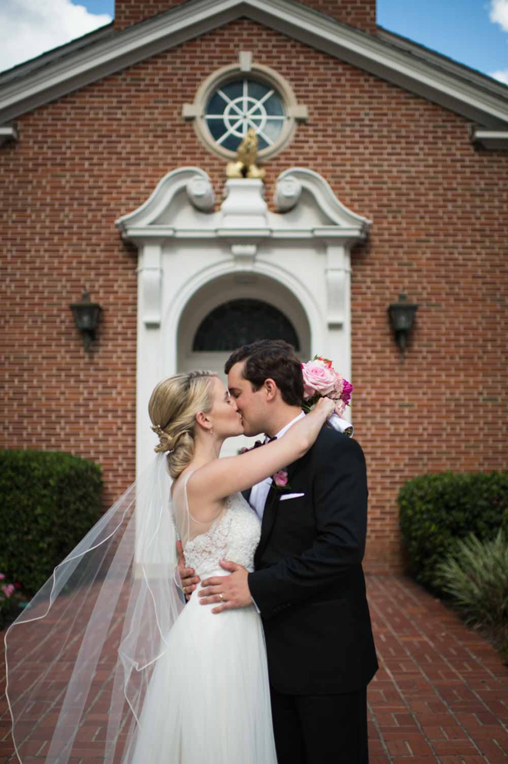 bride and kissing in front of
