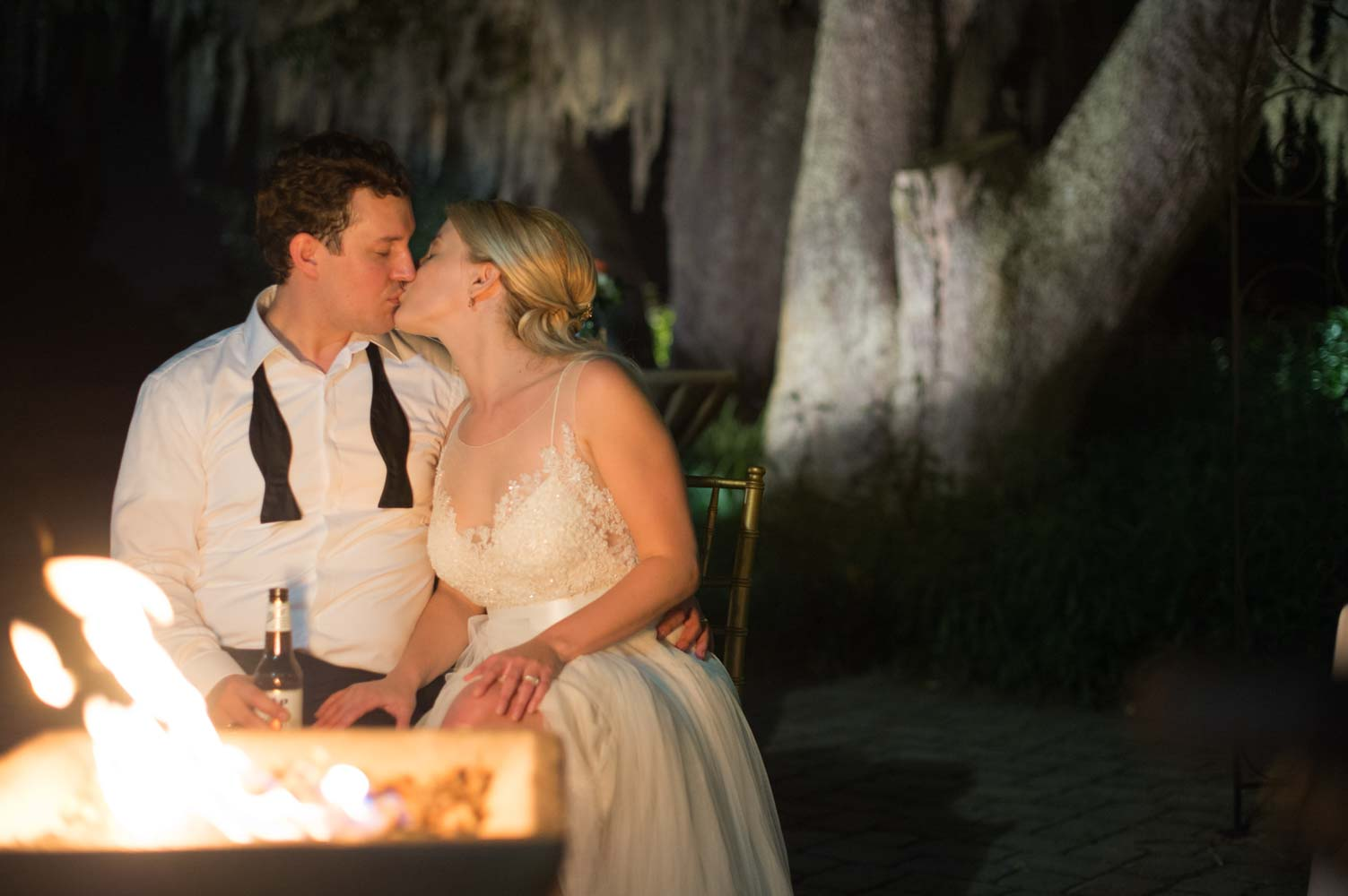bride and groom kissing in front of firepit at Historic Dubsdread