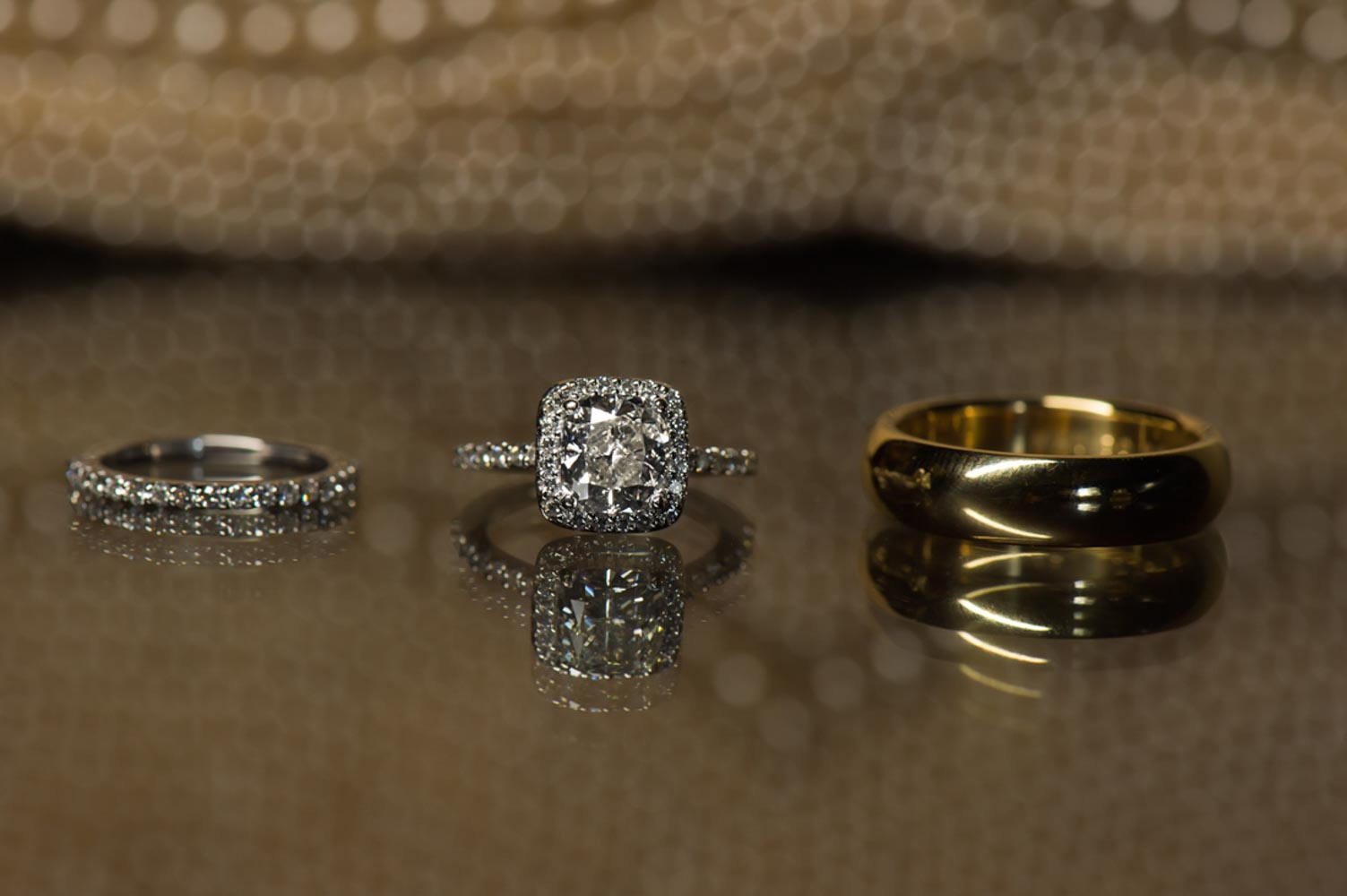 wedding rings and cushion engagement ring on table