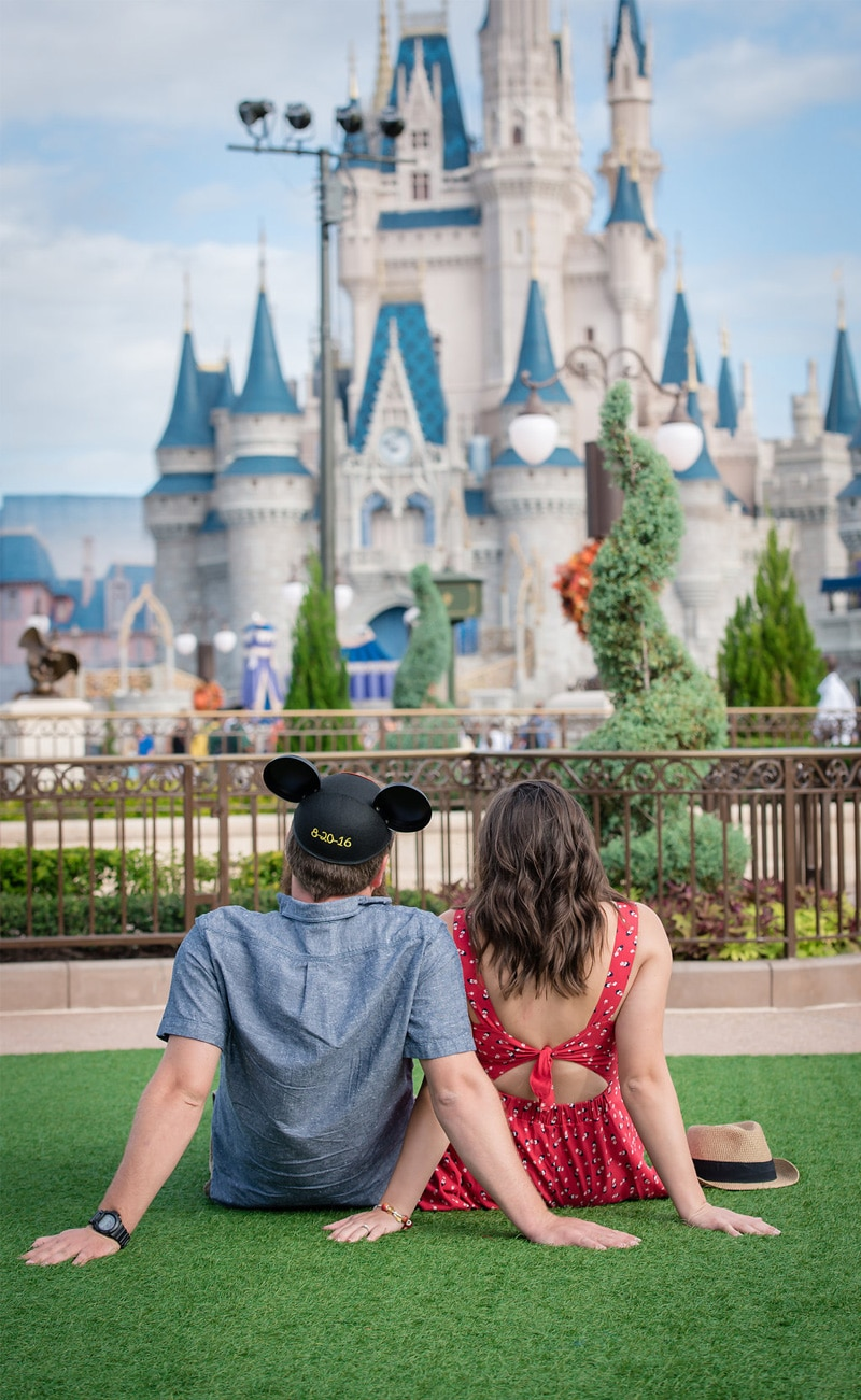 engaged couple sitting on lawn in front of Cinderella's Castle