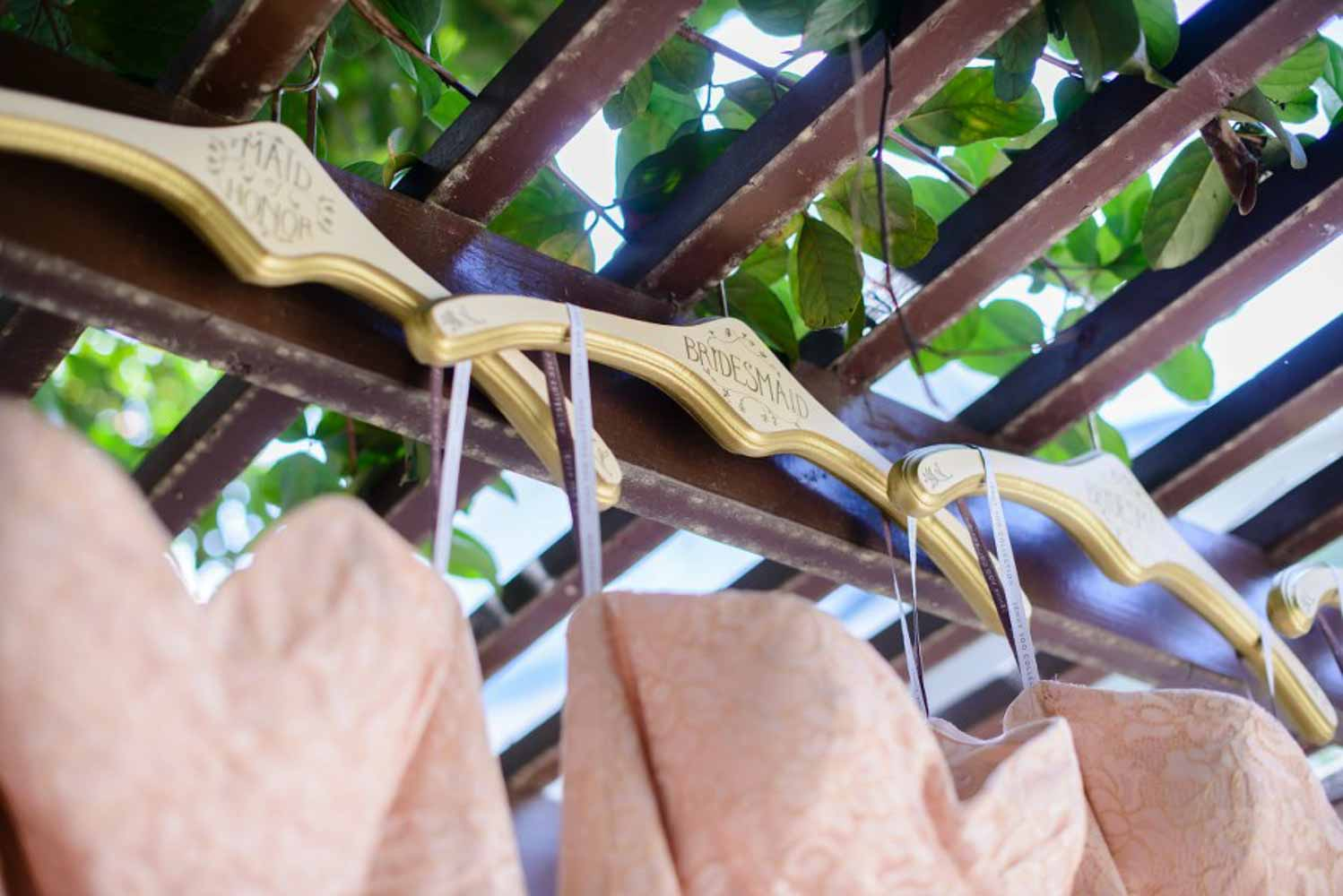 blush bridesmaid dresses hanging from pergola