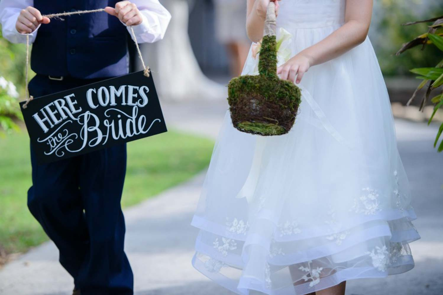 flower girl and ring bearer walking up the aisle for wedding ceremony