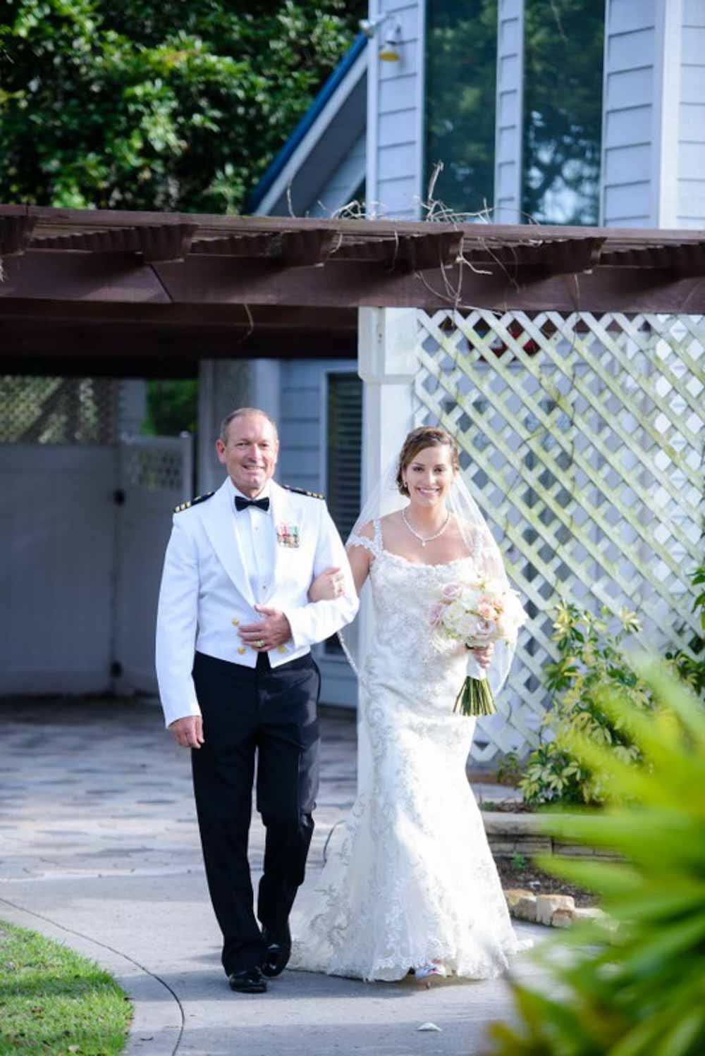 father in white military suite walk daughter up the wedding aisle