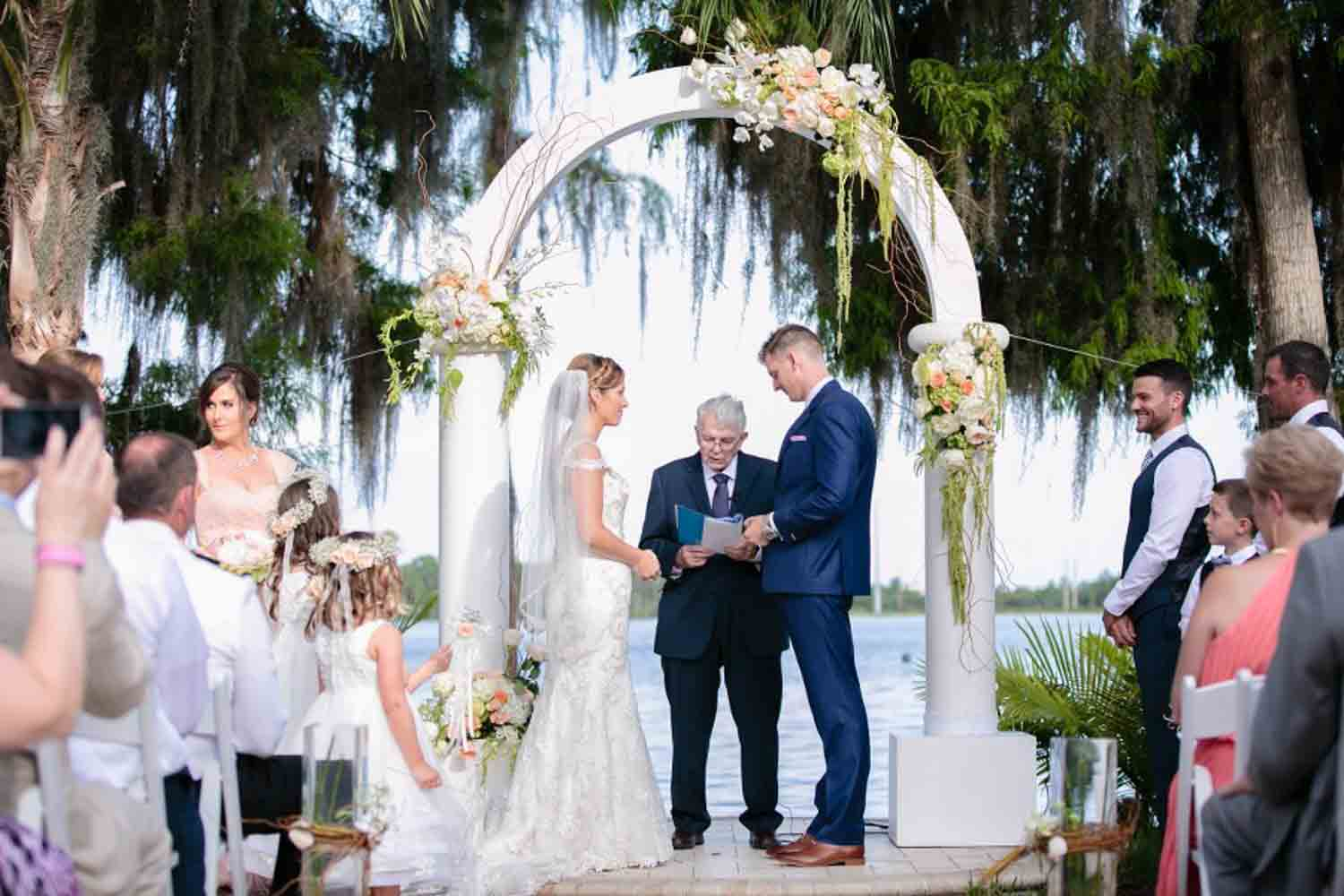 bride and groom under white wedding ceremony arch
