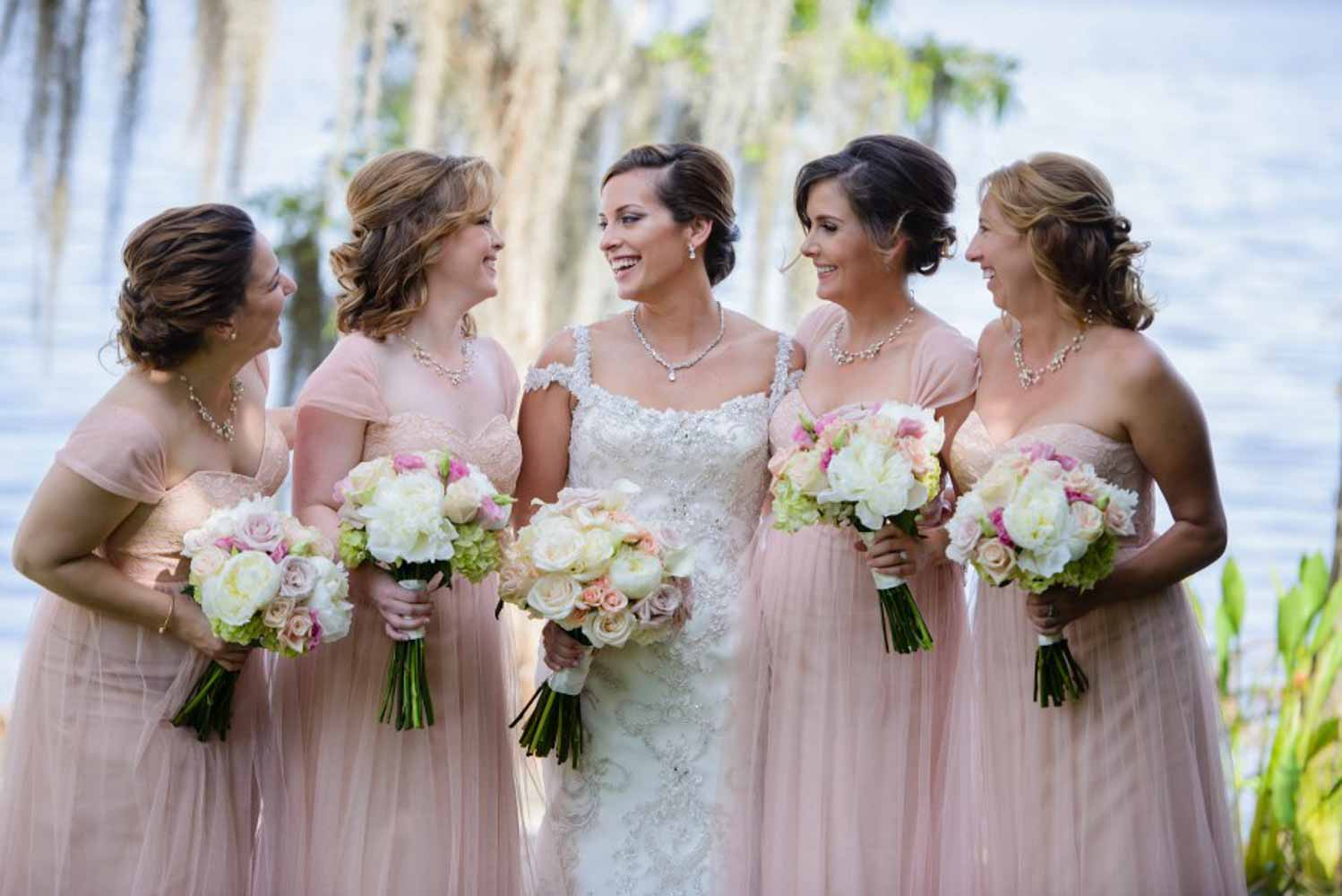 bride smiling with bridesmaids in blush dresses and holding bouquets