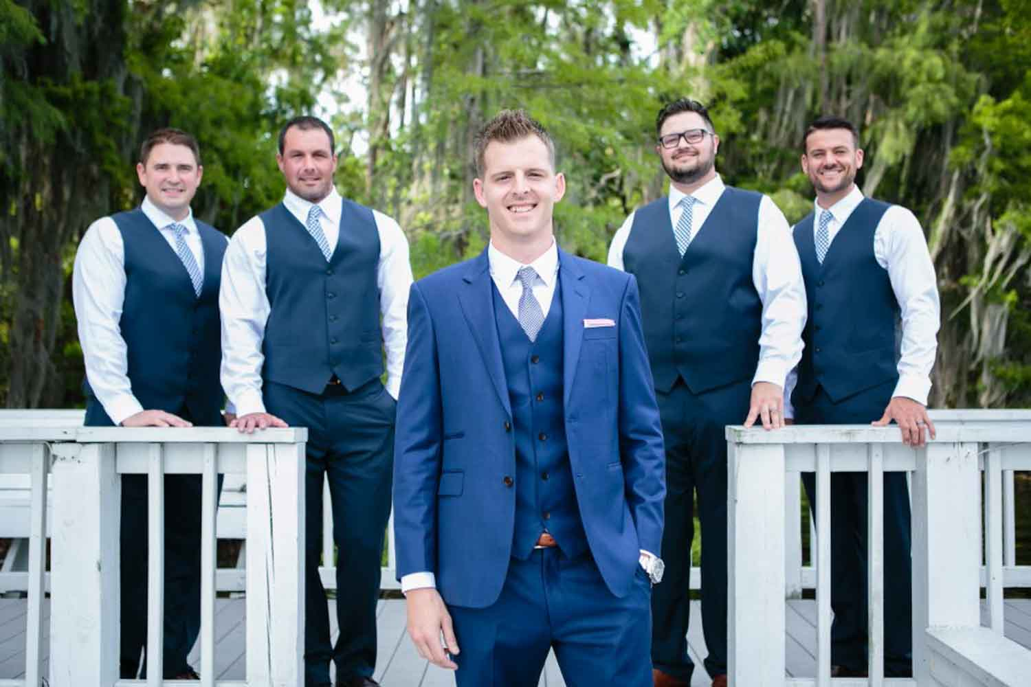 groom in blue suit with groomsmen in blue vests