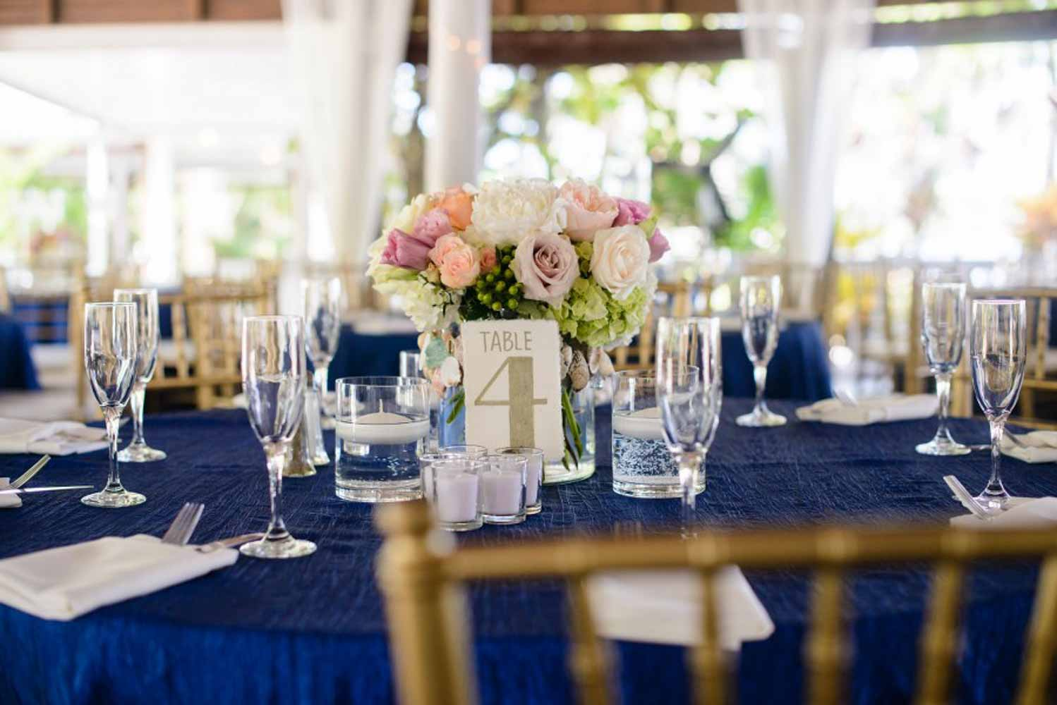 blush and white wedding centerpiece on reception table with navy tablecloth