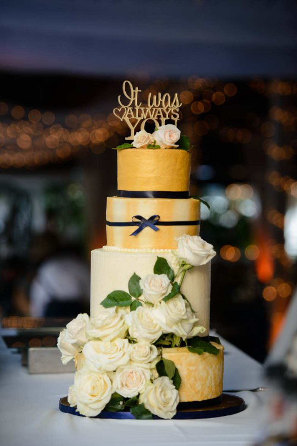 yellow four tiered wedding cake with white flowers