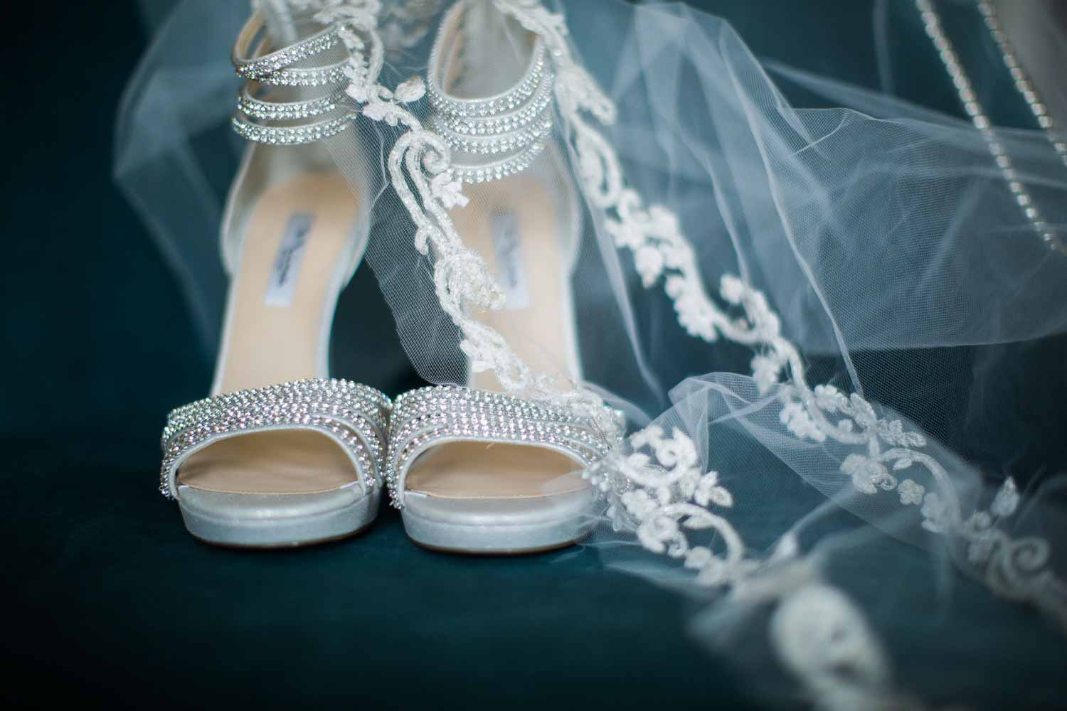 rhinestone bridal shoes next to wedding veil