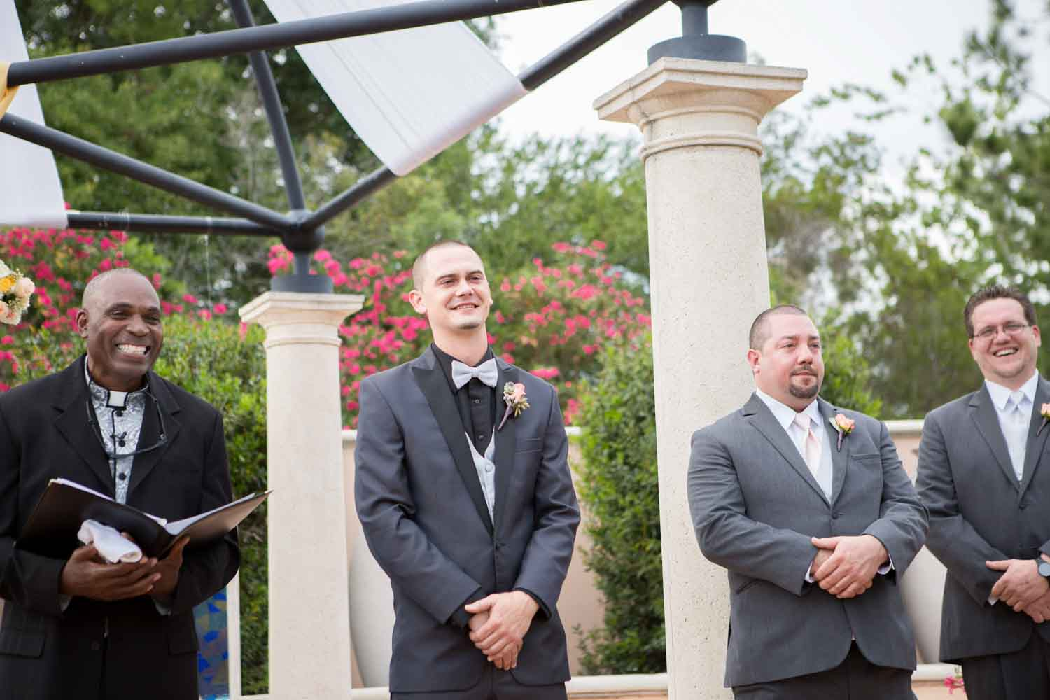 groom smiling while watching bride walk up aisle