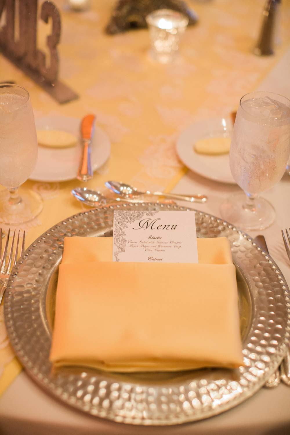 yellow naphkins and menu card on gold charger