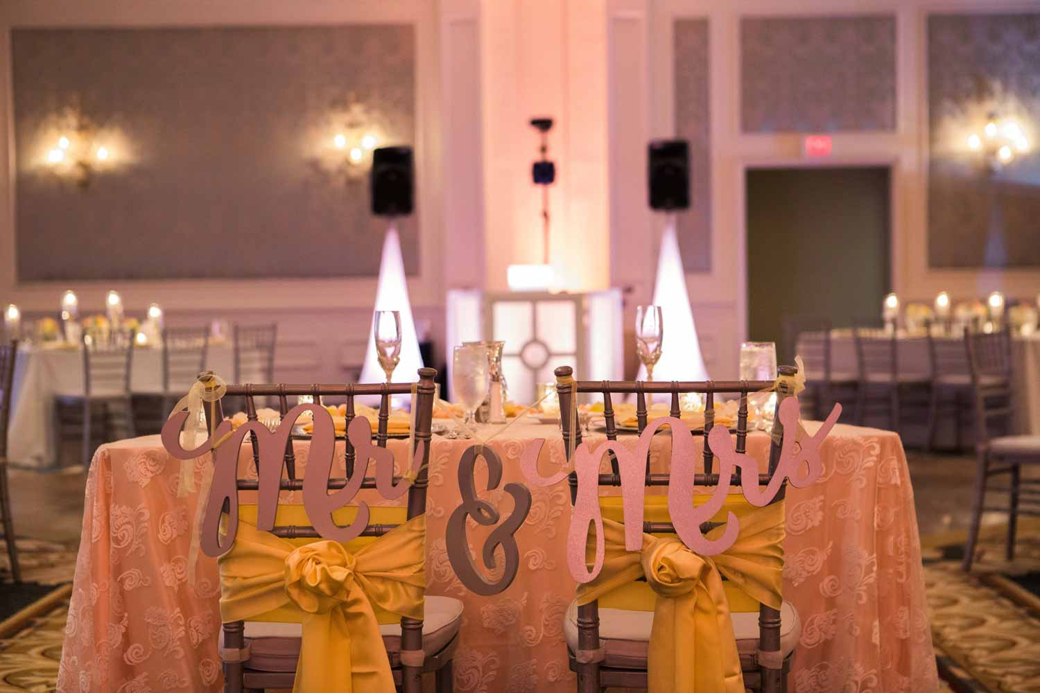 mr. and mrs. signs on sweetheart table chairs