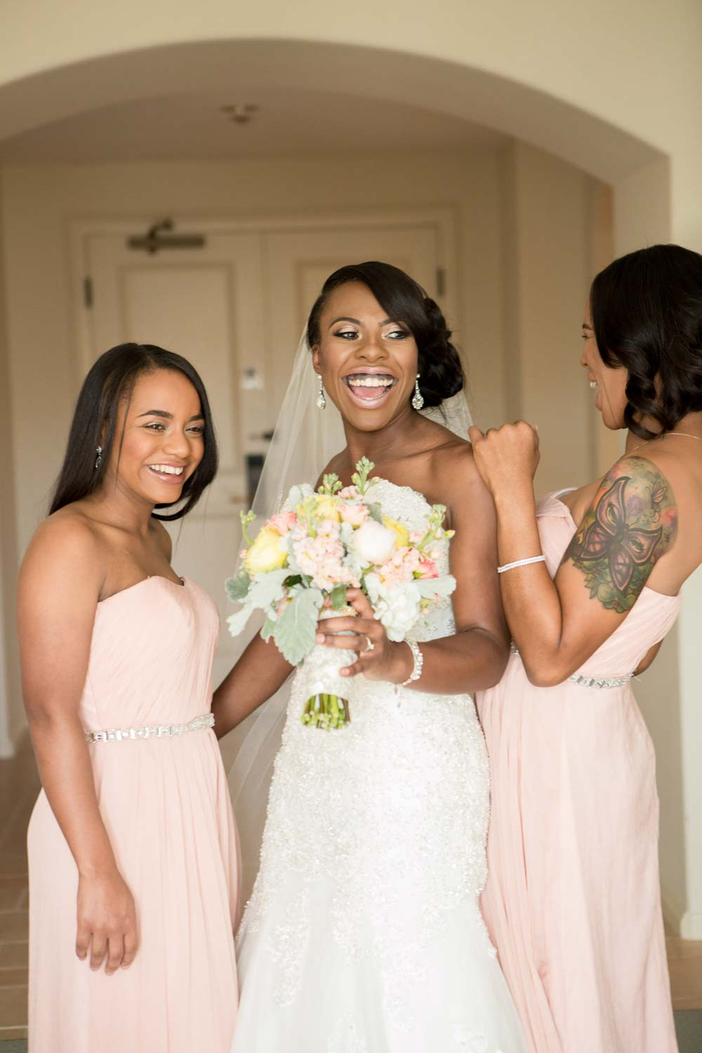 bridesmaids in blush dresses laughing with bride