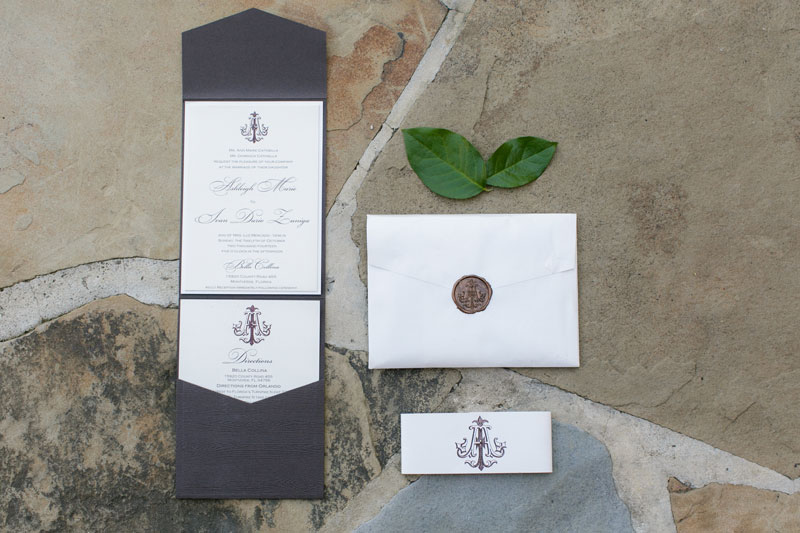 navy monogram wedding invitations laying on stone