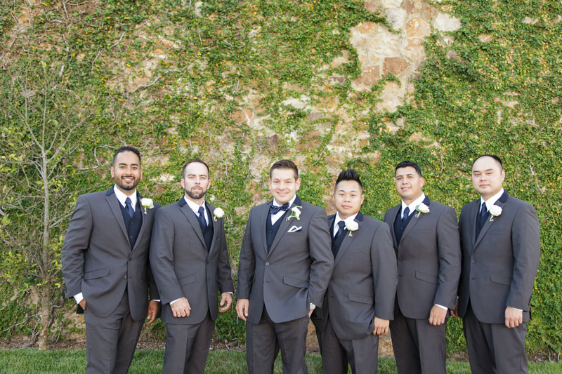 groom and groomsmen in gray suits in front of vined wall