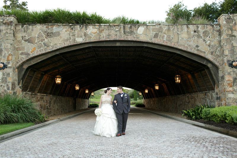 bride and groom walking under covered bridge