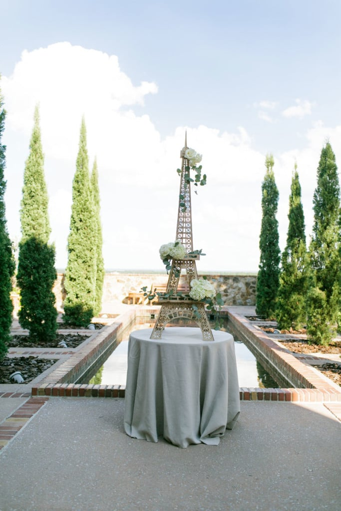 metal Eiffel tower decor in front of Bella Collina's pond