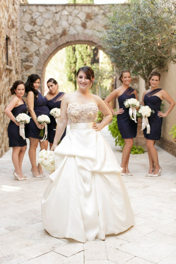 bride in walk way with bridesmaids in navy dresses behind her