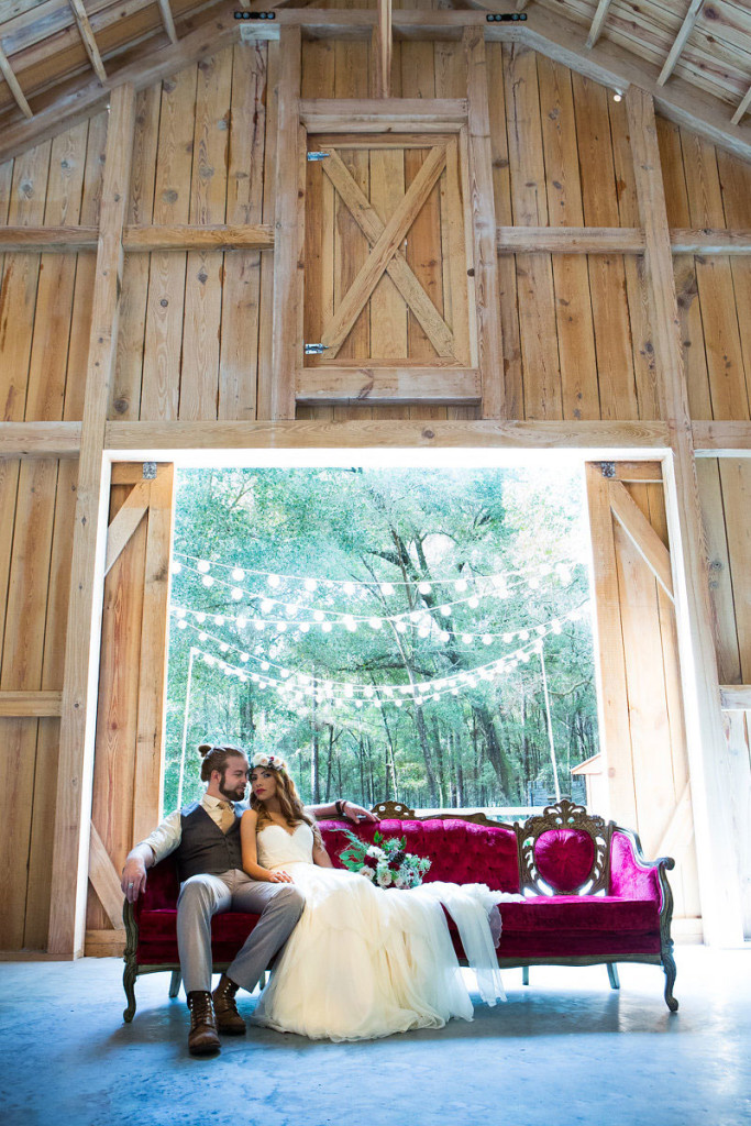 couple sitting on vintage sofa in barn