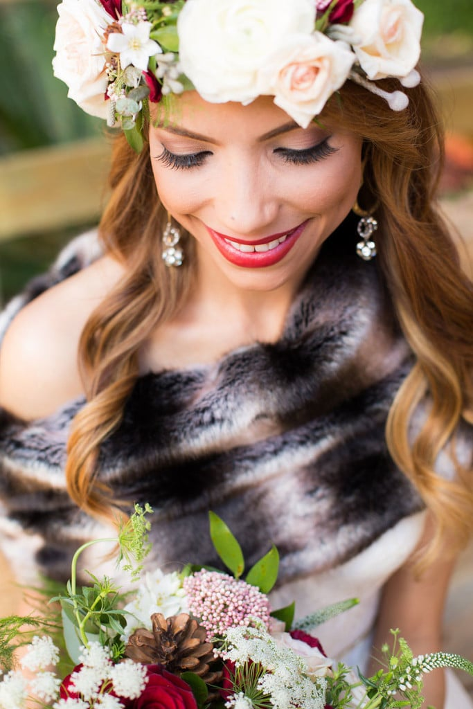bride looking at bouquet with fur shall on