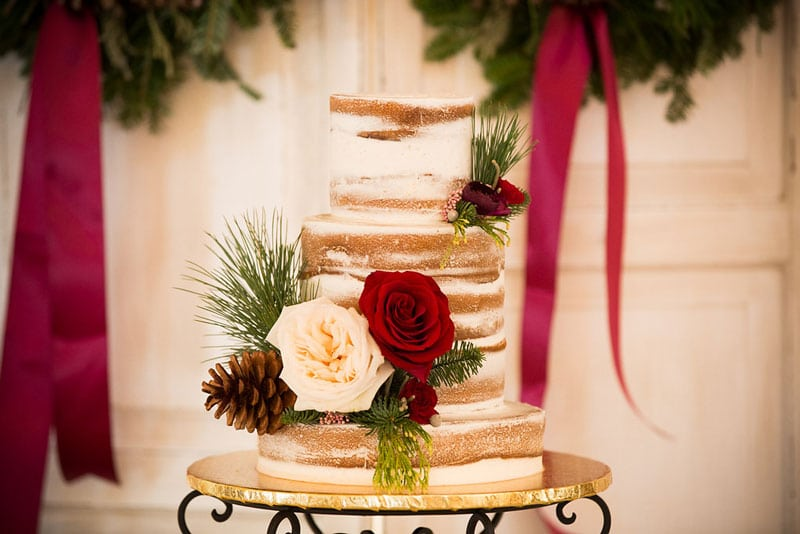 naked wedding cake with roses and pinecones