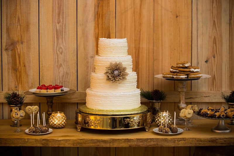 dessert buffet with white wedding cake at the center