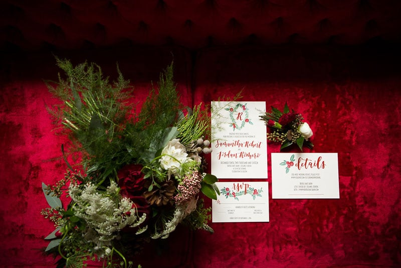 Christmas wedding invitations next to Christmas wreathe