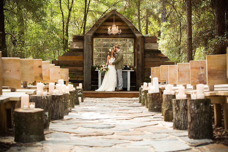 bride and groom kissing on rustic wedding alter