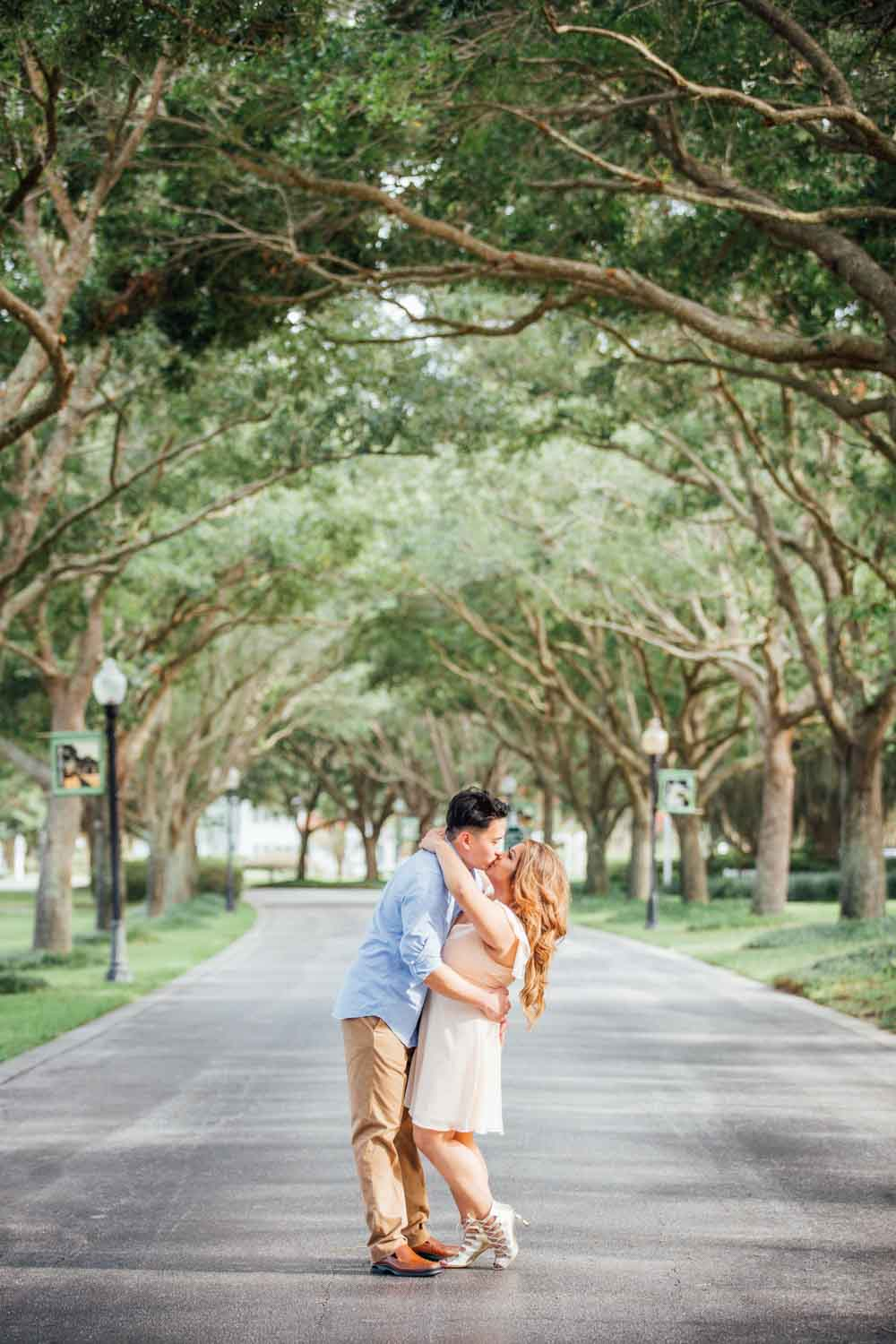 couple kissing under oak tree canopy