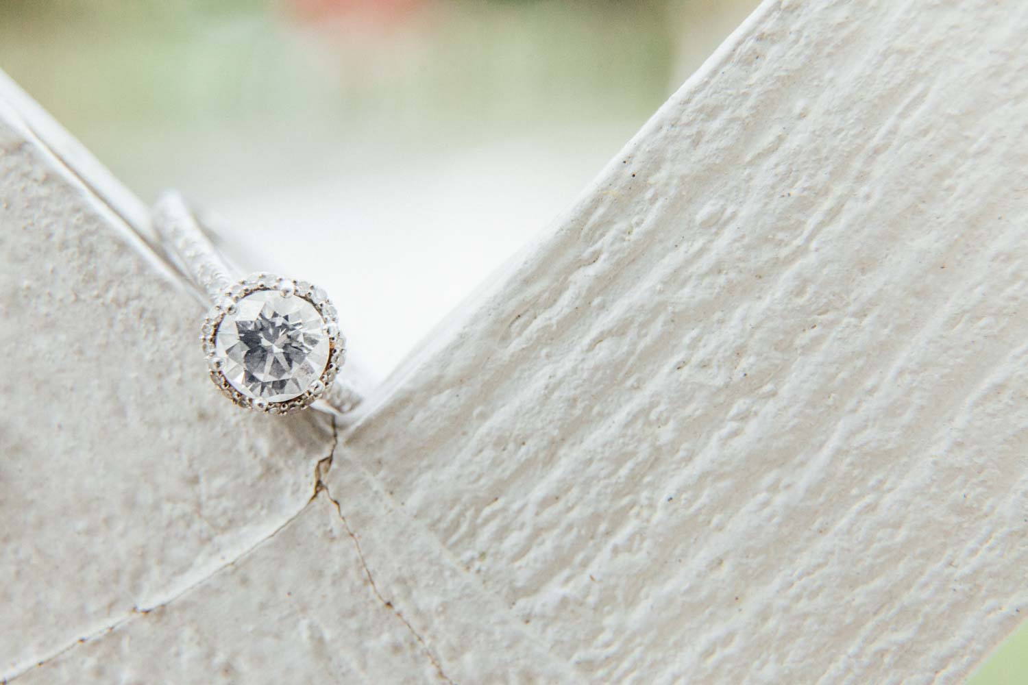 round halo engagement ring on white fence