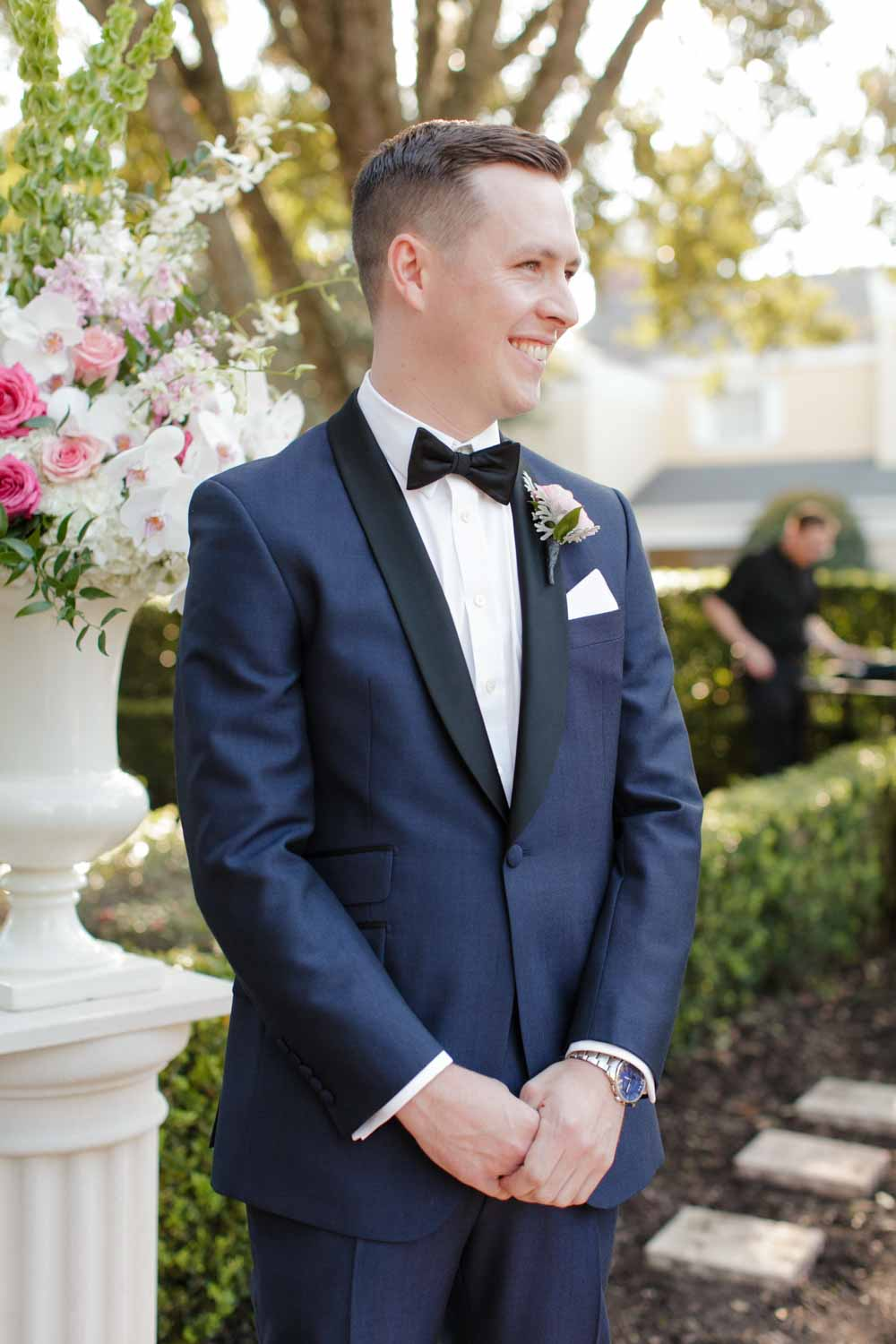 groom in navy tux smiling as bride walks up aisle