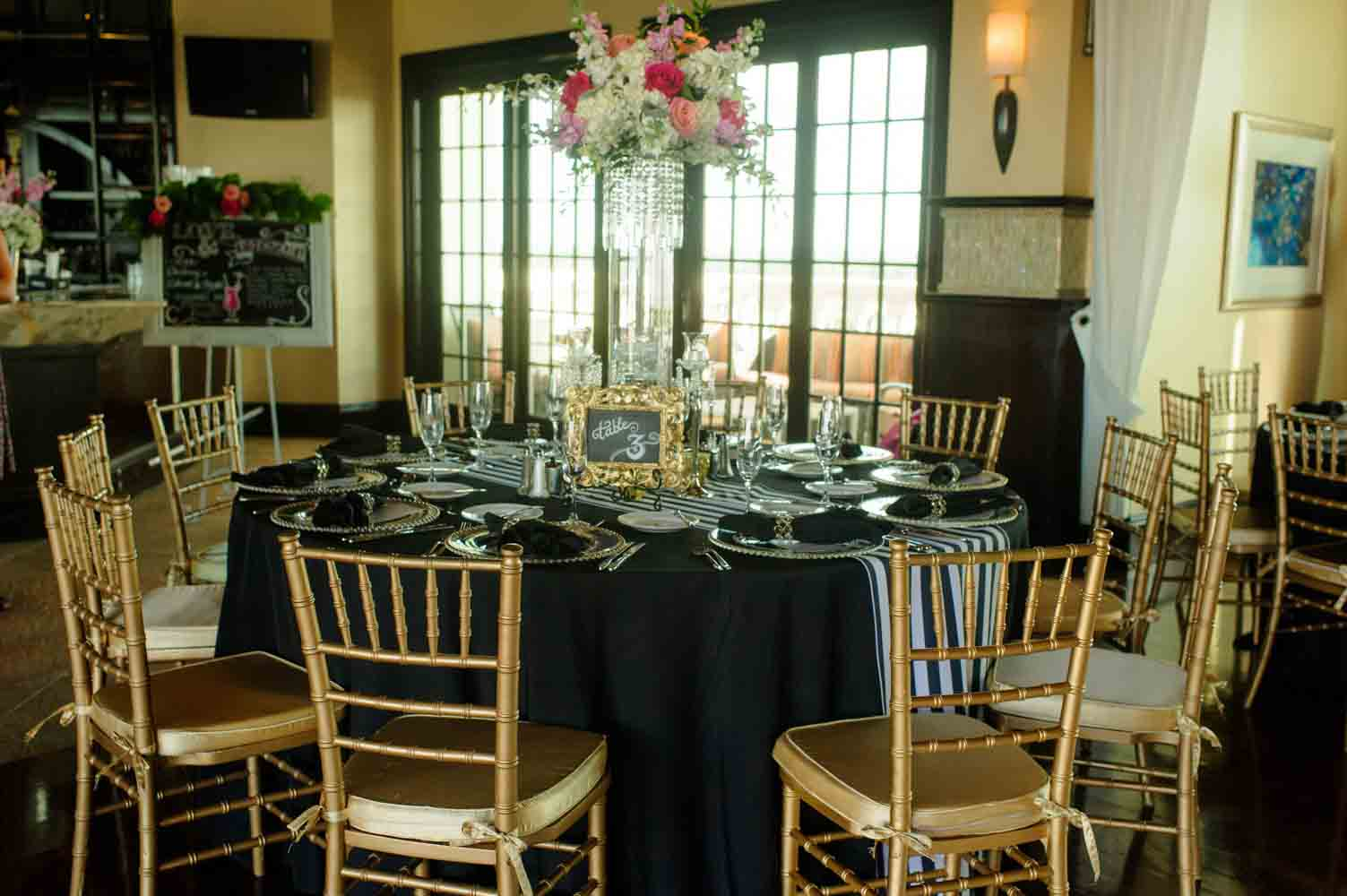 black and gold wedding reception tables with large floral centerpiece