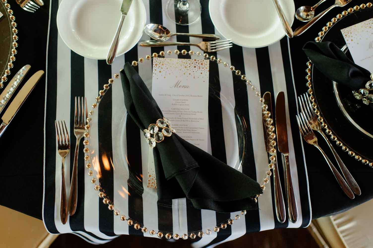 black napkin with gold ring on clear charger for Reunion Resort wedding