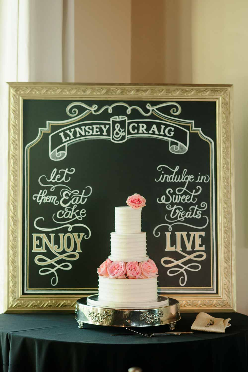 white buttercream wedding cake in front of chalkboard