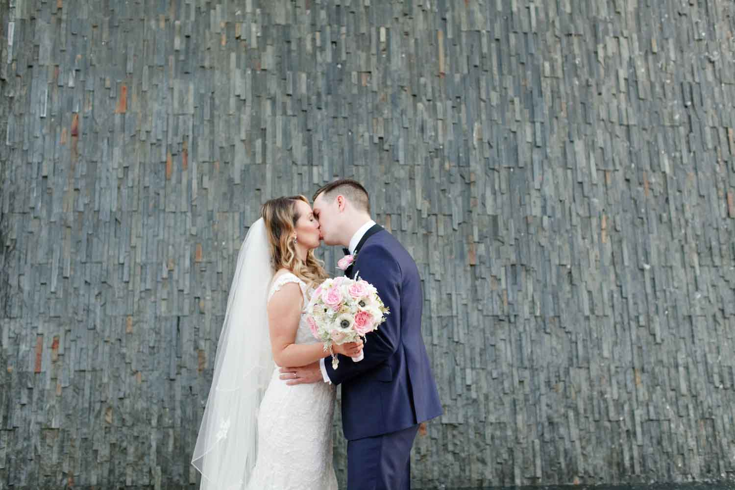 bride and groom kissing in front of waterfall