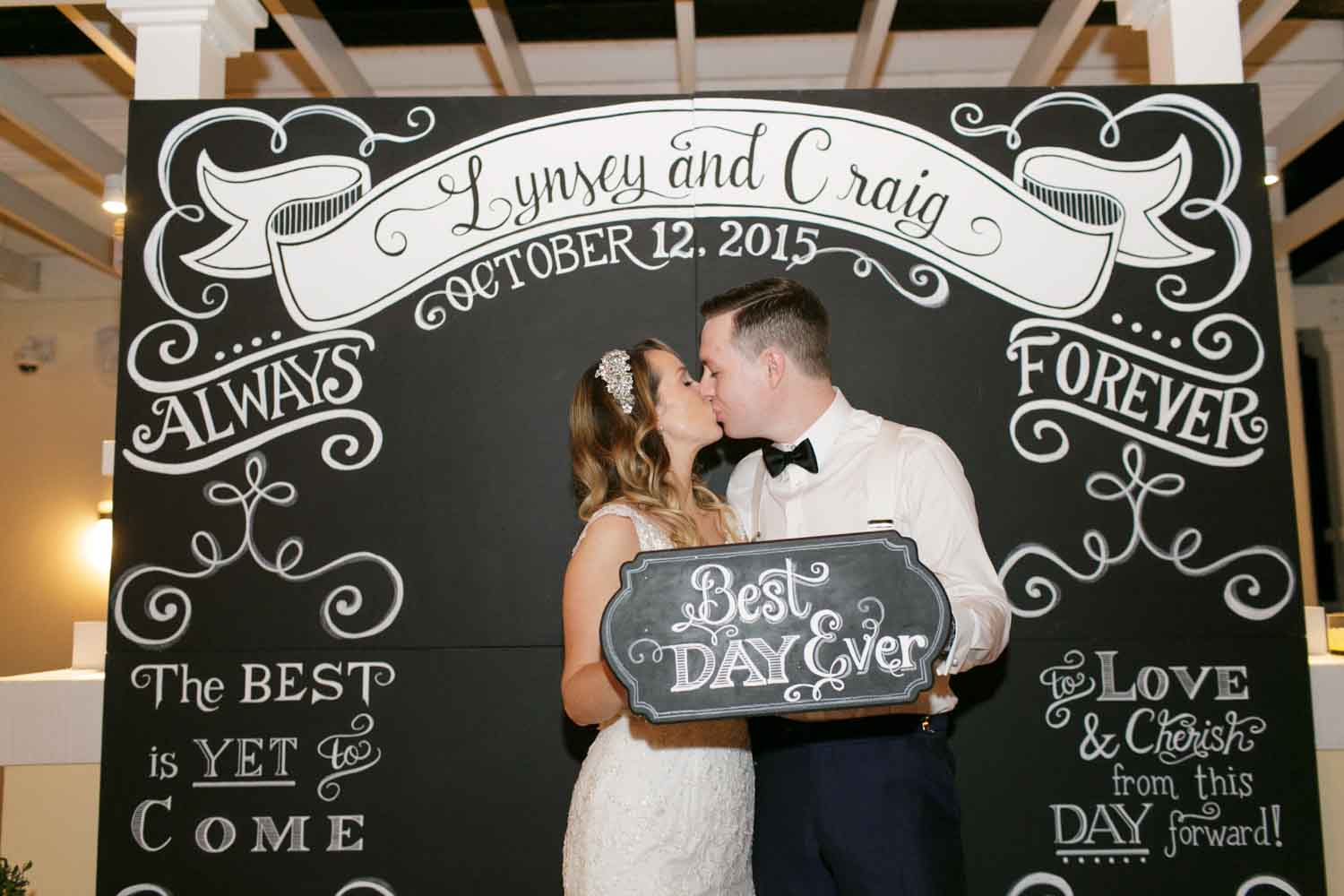 bride and groom kissing in front of chalkboard backdrop