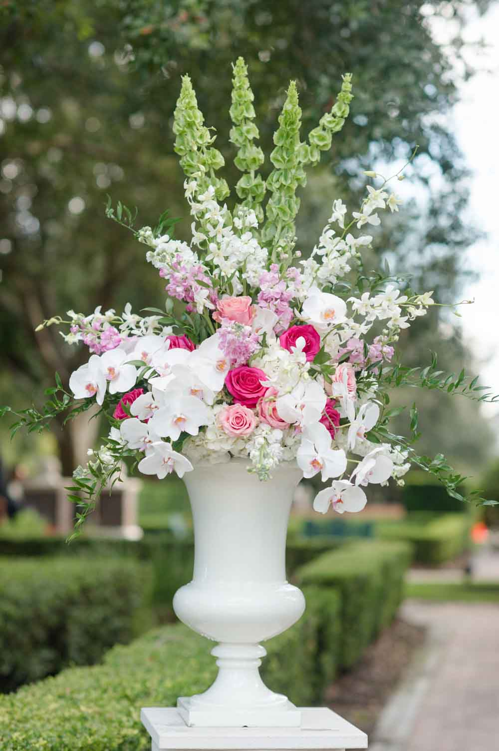 large wedding ceremony floral arrangement on white pedestal