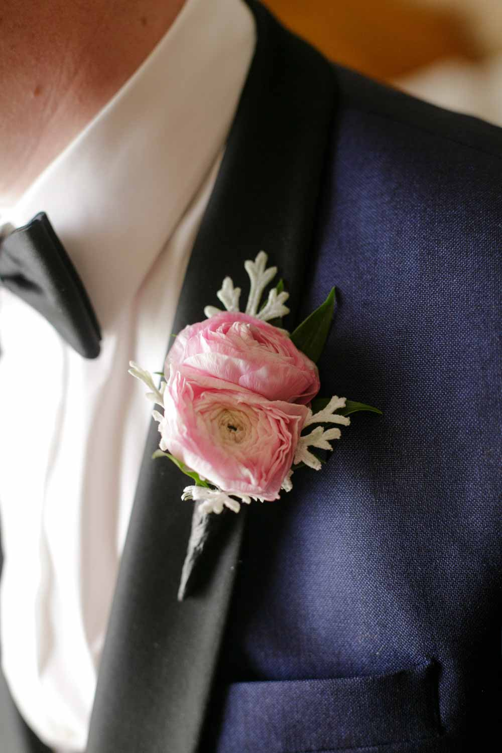 blush boutonniere on navy and black tux jacket