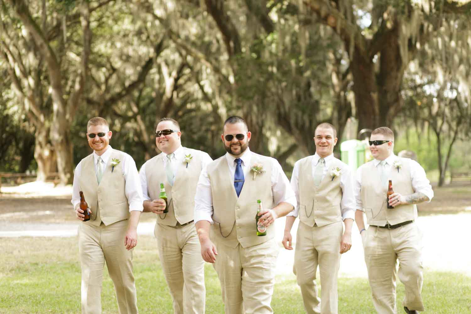 groomsmen wearing sunglasses and holding a beer walking to wedding