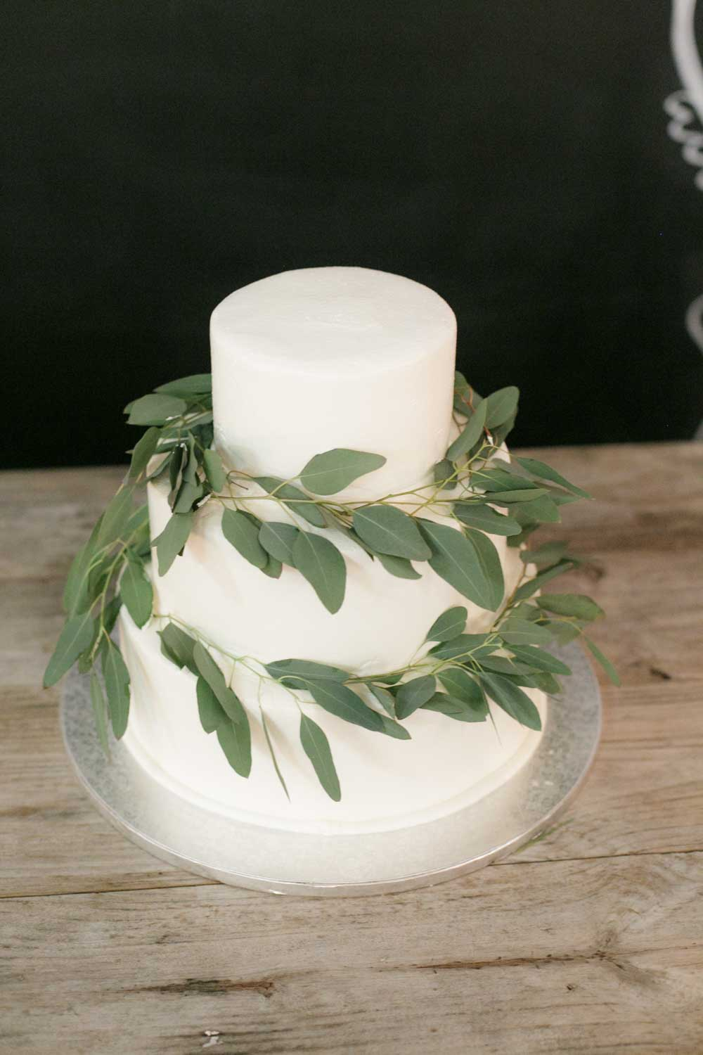 three tiered white buttercream cake with greenery on rustic table