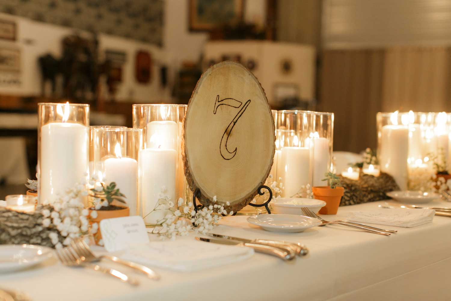 rustic wood slab table number next to pillar candles