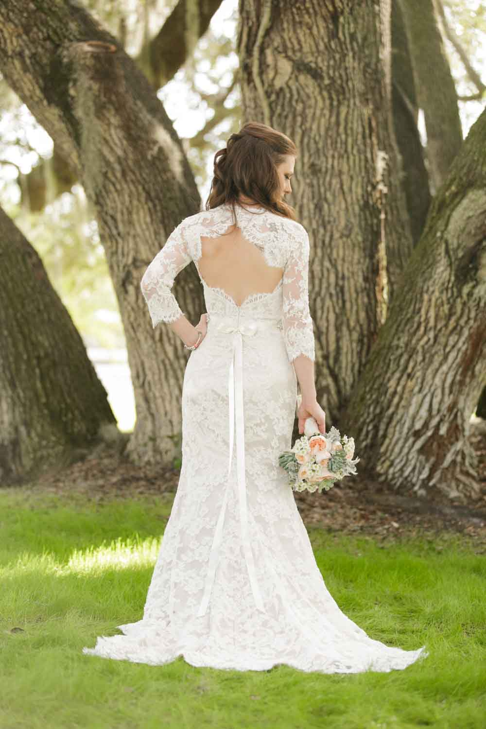 bride in lace gown holding bouquet and looking down