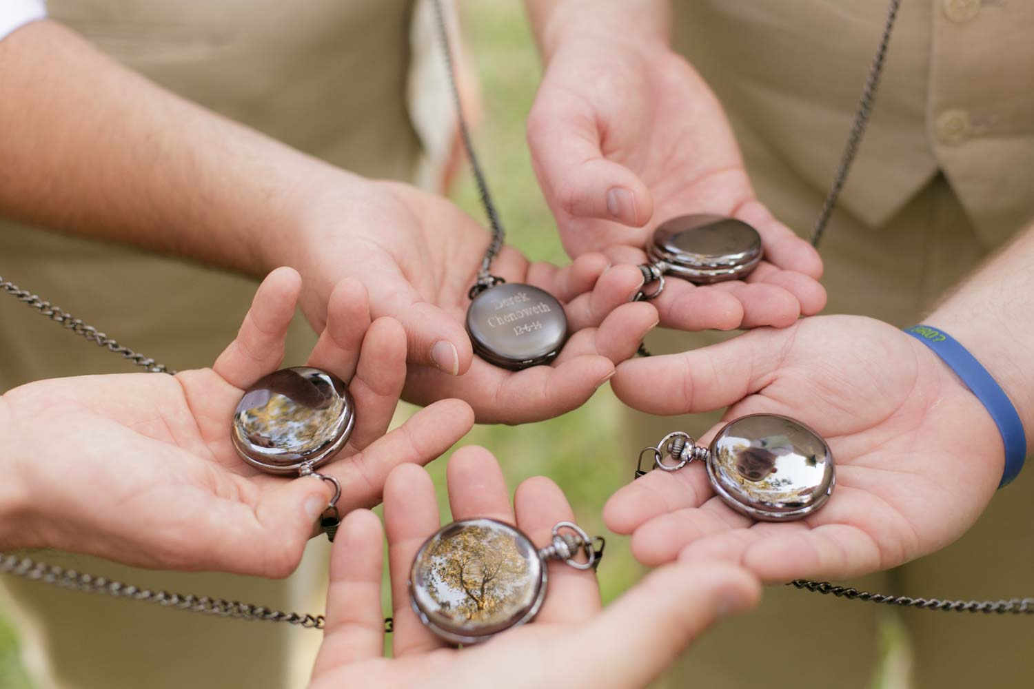 groomsmen holding pocket watch gifts for wedding