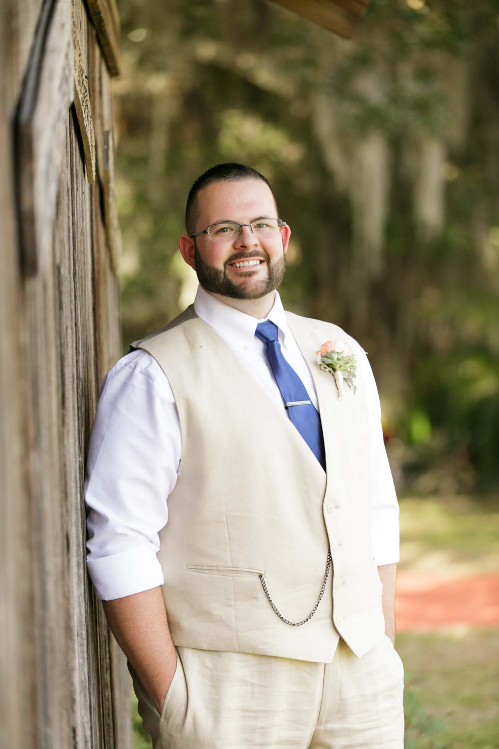 groom in khaki vest and blue tie smiling by wood fence