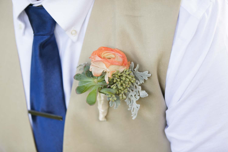 coral and succulent boutonniere on khaki vest
