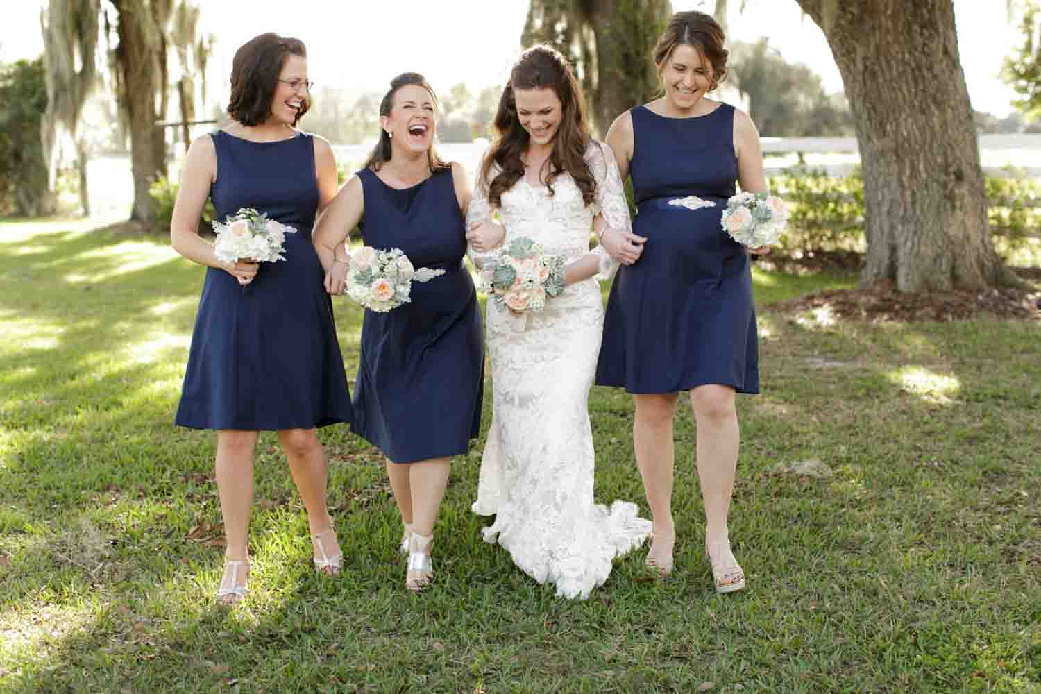 bridesmaids in navy dresses walk and laughing with bride